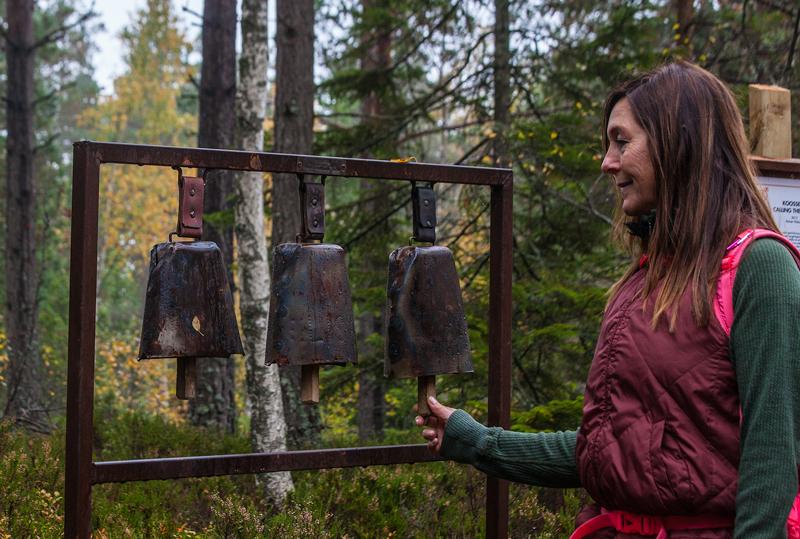 Kvinna håller i koklocka på skulptur på bergslasleden