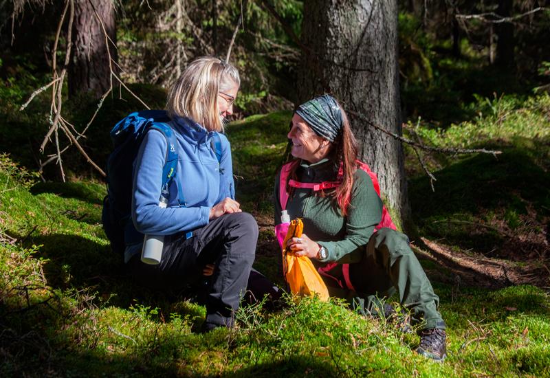 Två kvinnor sitter i mossan vid etapp 17 på Bergslagsleden