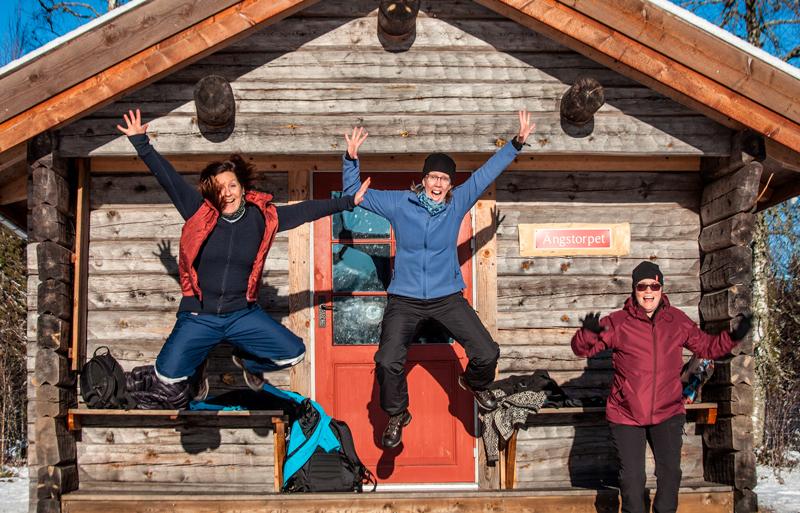 3 kvinnor hoppar framför en stuga i Gårdsjötorp